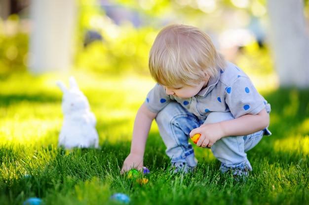 イースターの日に春の庭でイースターエッグを捜す少年。ごちそうを祝う伝統的なウサギとかわいい子