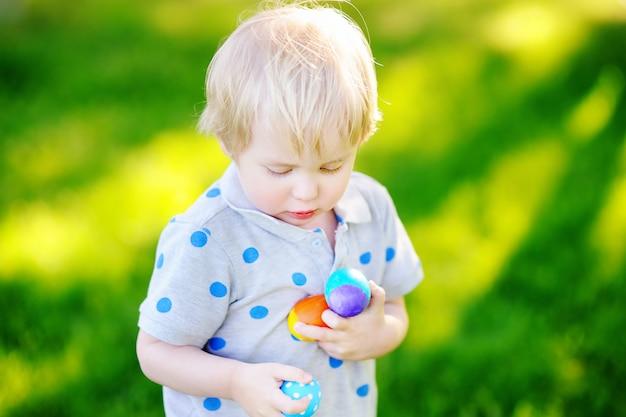 イースターの日に春の庭でイースターエッグを捜す少年。