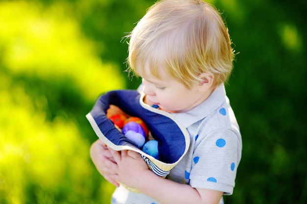 イースターの日に春の庭で卵を探している少年。ごちそうを祝う伝統的なイースターエッグとかわいい子