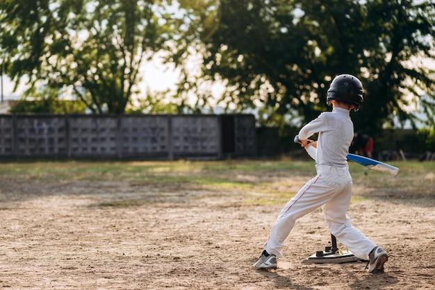 Маленький мальчик в бейсбольном шлеме бьет по мячу