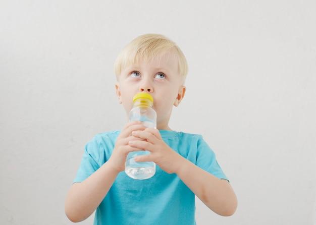 Маленький мальчик в синей футболке пьет воду