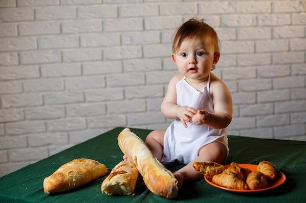 帽子をかぶってパンを持った小さな男の子。台所で料理人に扮した小さな子供。