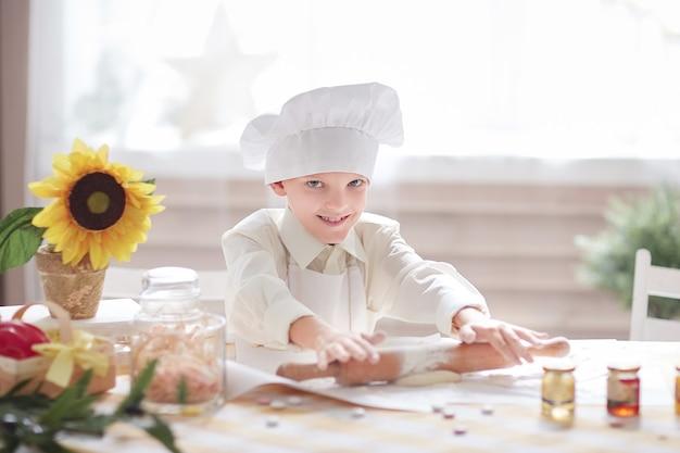 シェフの帽子をかぶった男の子が生地を転がします。趣味と興味