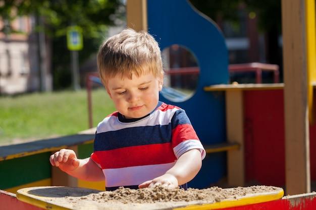 컬러 티셔츠를 입은 어린 소년이 샌드박스에서 놀고 있다