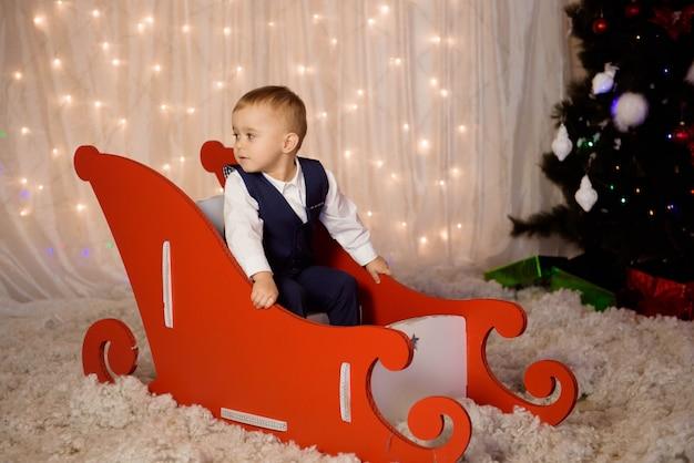크리스마스 트리 근처에 크리스마스를 기다리는 의상을 입은 어린 소년