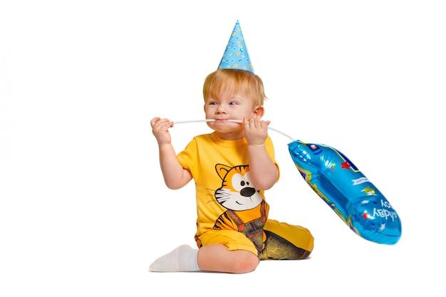 흰색에 고립 된 풍선 축제 모자에 작은 소년