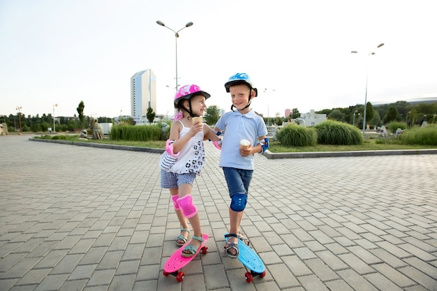 헬멧을 쓴 어린 소년이 공원에서 소녀를 안고 스케이트 보드를 타고 아이스크림을 먹습니다.