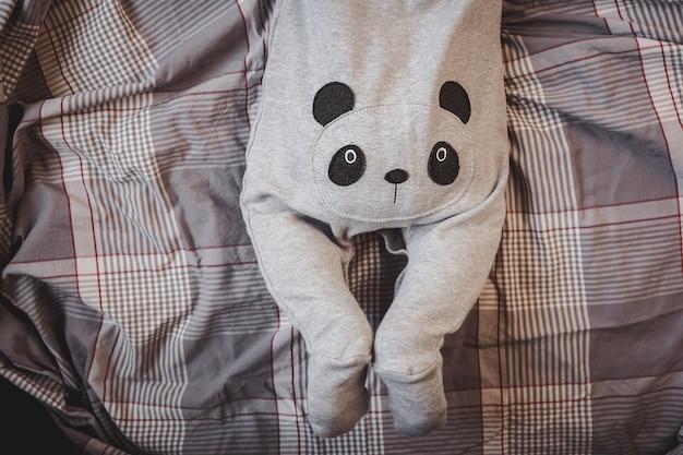 Маленький мальчик в костюме панды лежит на кровати.