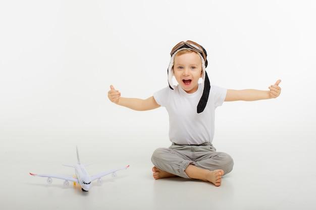 パイロットの帽子と白い背景の上の飛行機と小さな男の子