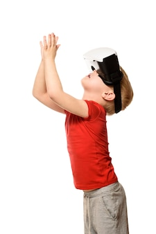 Маленький мальчик в красной рубашке переживает виртуальную реальность, держась за руки перед собой. изолировать на белом фоне. концепция технологии.