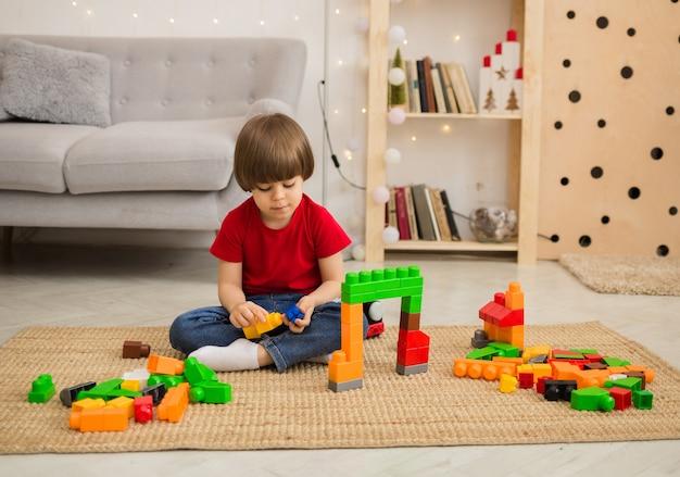 빨간 티셔츠와 청바지에 어린 소년이 방에있는 소파 옆에있는 바닥에 다채로운 건설 키트로 재생됩니다.