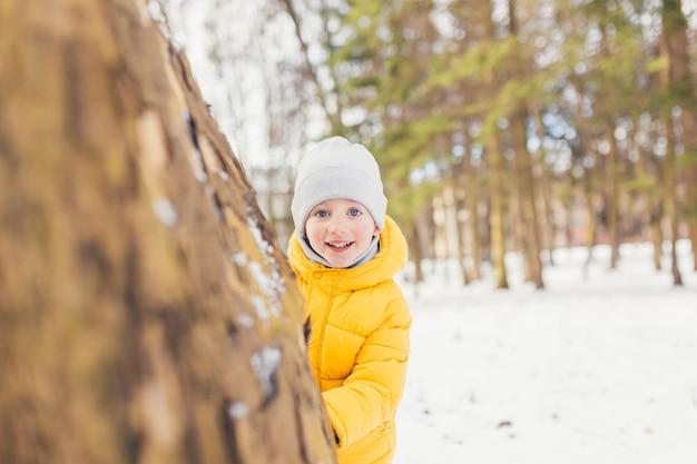 Маленький мальчик на прогулке в парке со своей семьей зимой, веселится и наслаждается снегом
