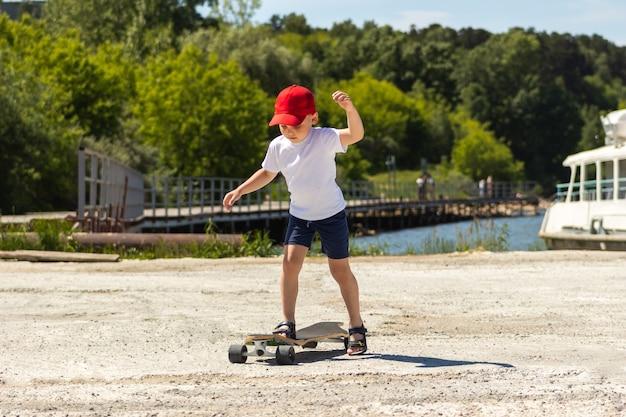 흰색 티셔츠와 빨간 모자를 쓴 어린 소년은 배경에 부두가 있는 스케이트보드를 탄다