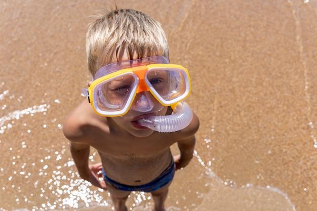 黄色のダイビングマスクとシュノーケルの男の子。砂浜を背景に子供が立ちます。ウォーターゲームで楽しい休暇を。