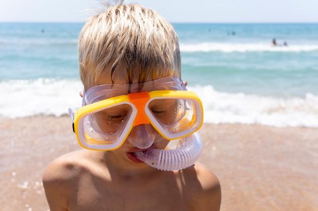 黄色のダイビングマスクとシュノーケルの男の子。子供は海を背景に立っています。ウォーターゲームで楽しい休暇を。