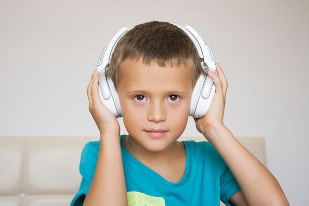ヘッドフォンを着ている青いシャツを着た小さな男の子。子供は音楽を楽しんでいます。
