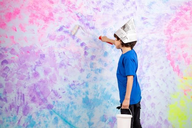 青いtシャツの壁の絵画の小さな男の子