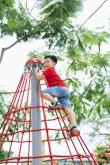 キャップの小さな男の子が公園のジャングルジムに登る