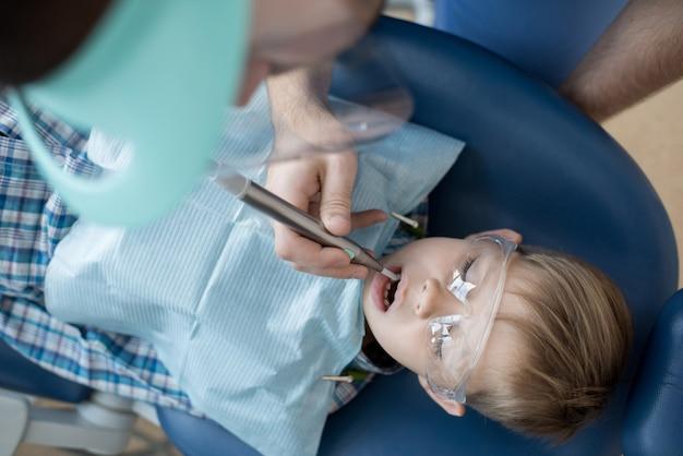 Маленький мальчик в стоматологическом кресле сверху
