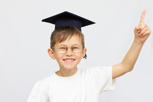 Маленький мальчик в выпускной шляпе и с поднятым указательным пальцем на белом фоне