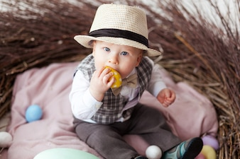 Little boy in hat sitting in nest and eating easter egg.