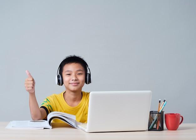 Маленький мальчик в наушниках учится онлайн с помощью ноутбука