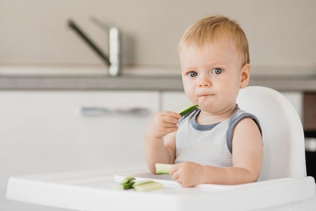Маленький мальчик в стульчике ест