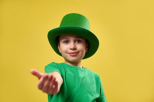 レプラコーンの緑のアイルランドの帽子をかぶった少年がカメラに向かって手のひらを伸ばします