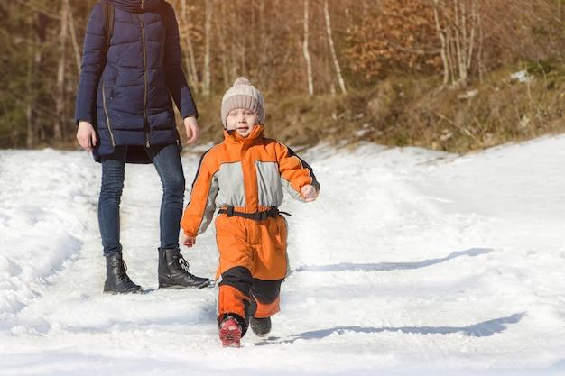 Маленький мальчик в комбинезоне убегает от матери. зимний снежный день в хвойном лесу.