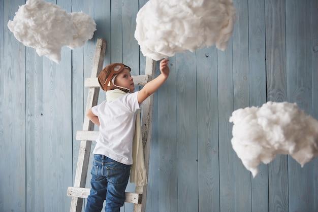 スタジオの梯子の上に立っているパイロット帽子の少年。天国に到達します。雲の概念に触れる