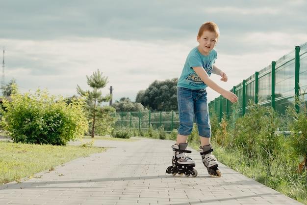 Маленький мальчик в защитном снаряжении и роликах стоит на дорожке в парке, низкий угол обзора