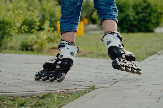 保護具とローラーの小さな男の子が公園の歩道に立っている、ローアングルビュー