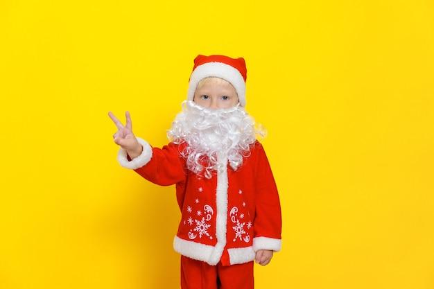 흰 수염을 가진 빨간 크리스마스 의상을 입은 어린 소년이 손으로 승리 제스처를 보여줍니다