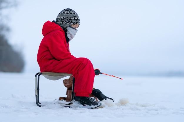 冬の釣りに赤いオーバーオールの小さな男の子。折りたたみ椅子に座っています。釣り竿の手に。
