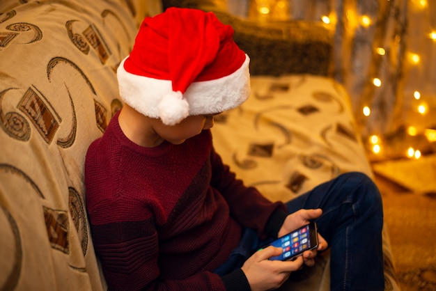 Маленький мальчик в красной шляпе санта-клауса играет в игры на своем мобильном телефоне