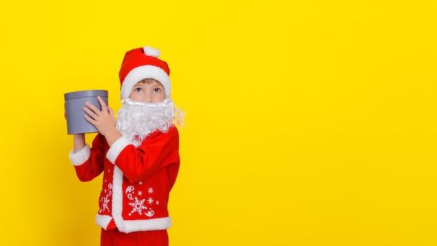 산타클로스 옷을 입고 손에 둥근 선물 상자를 들고 인공 수염을 가진 어린 소년