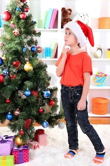 サンタの帽子をかぶった小さな男の子がクリスマスツリーの近くで夢を見る