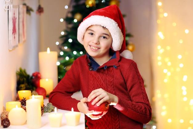 部屋の暖炉の近くのサンタの帽子の小さな男の子