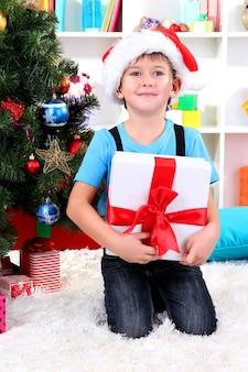 Маленький мальчик в шляпе санты сидит возле елки с подарком в руках