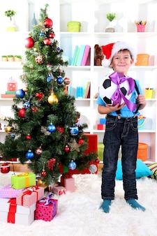サンタの帽子をかぶった小さな男の子がサッカーボールでクリスマスツリーの近くに立っています