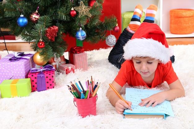 Маленький мальчик в шляпе санта пишет письмо деду морозу