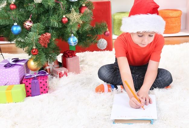 サンタの帽子をかぶった少年がサンタクロースに手紙を書く