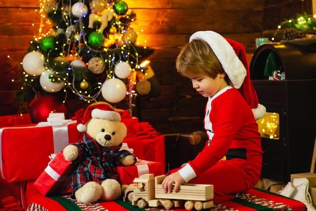 暖炉のそばでおもちゃで遊ぶサンタのスーツを着た小さな男の子