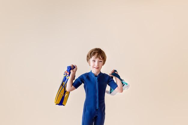 스쿠버 마스크와 모래 배경에 스노클링 어린 소년.