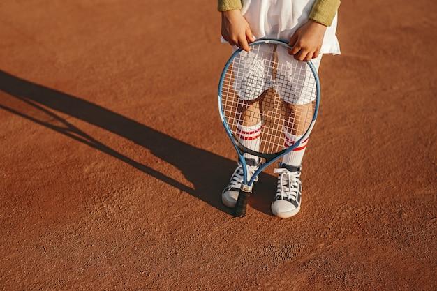 Маленький мальчик в спортивной одежде держит ракетку на теннисном корте
