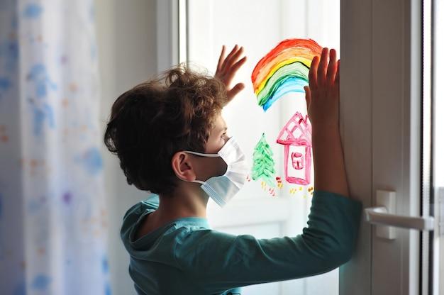 手術マスクの小さな男の子は、手を上げて塗装された窓に立っています