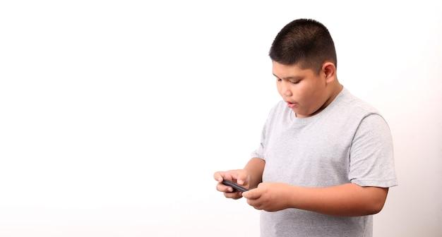 スタジオで白い背景にスマートフォンを提示するtシャツの小さな男の子。