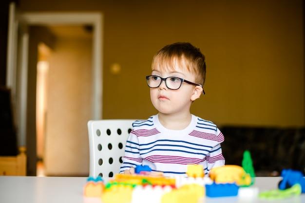 Маленький мальчик в очках с синдромом рассвета, играя с разноцветными кирпичами
