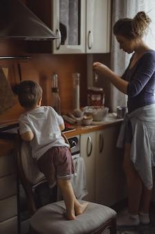 부엌에서 어린 소년은 엄마가 요리하는 데 도움이됩니다. 아이는 요리에 관여합니다.