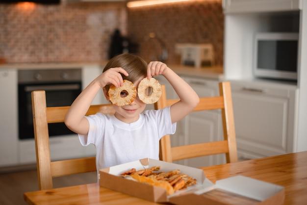台所で小さな男の子はドライパイナップルのリングで遊ぶ
